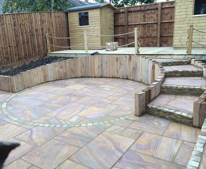 Rainbow Sandstone Patio With Oak Sleeper Walls and Decking in Aylesbury